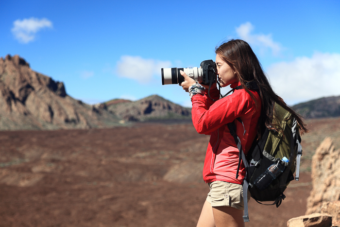 A female photographer adjusting her camera settings in a rocky landscape with blue skies
