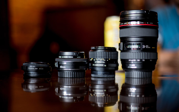 four different types of photography lenses on a table with reflections