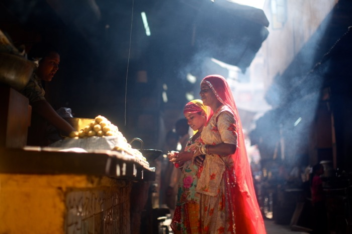 Women buying food in a market - street photography camera settings