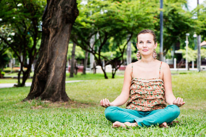 A woman mediating outdoors in a park