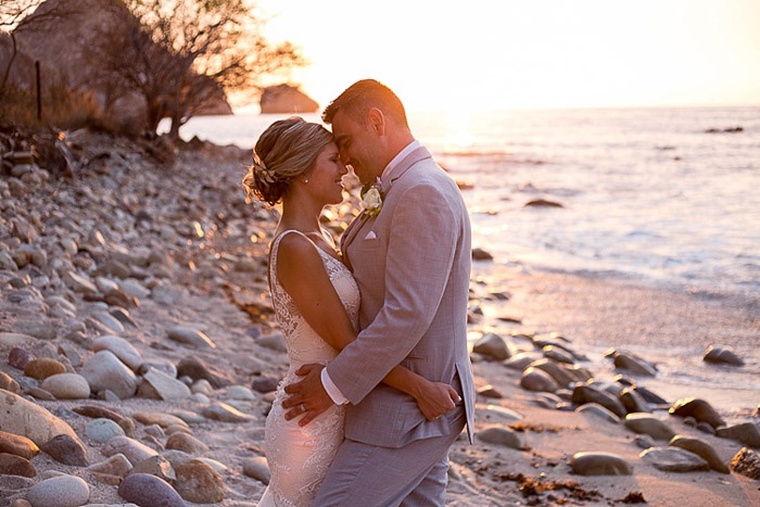 A newlywed couple embracing on a beach
