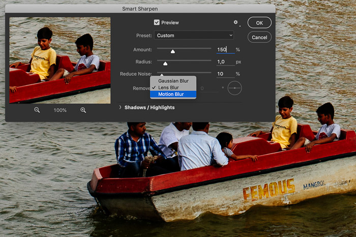 Screenshot of editing a picture in Photoshop showing a row boat in India. The Smart Sharpen setting are open in this screenshot and the Motion Blur is selected from the drop down menu.