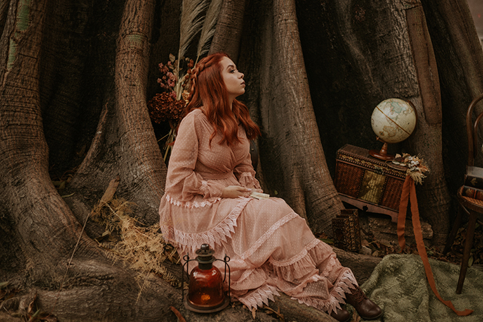 conceptual fantasy themed portrait of a female sitting in the woods