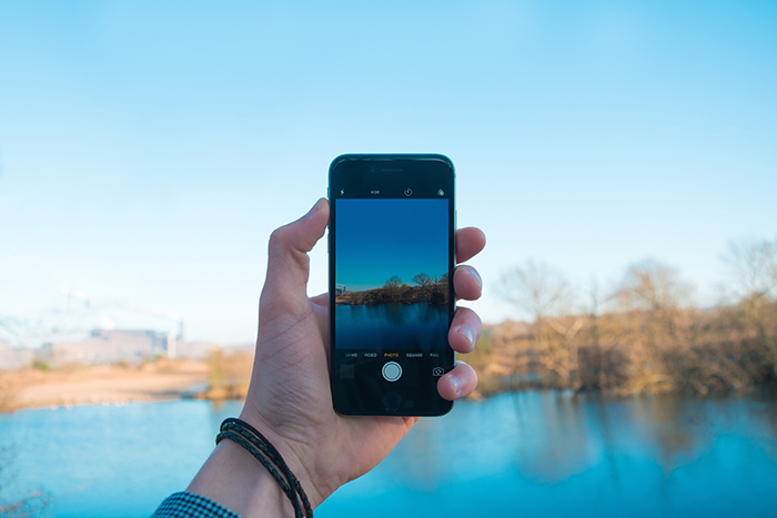 a person taking a landscape photo with a smartphone
