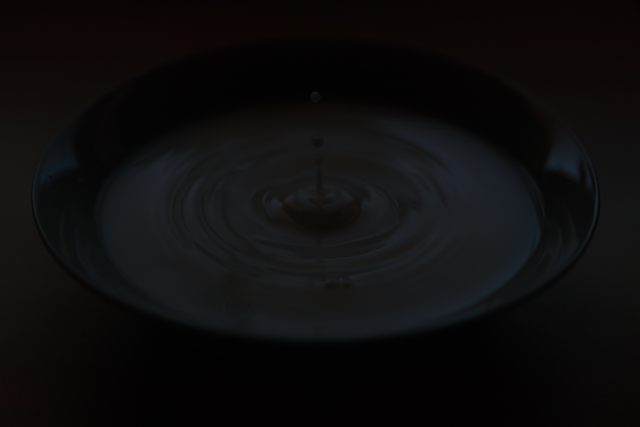 Illustration photo of a drop falling on a water surface. The goal was to freeze the drop's motion using a short exposure time. Even though a minimal f-stop was used, the photo is still underexposed due to a lack of light.