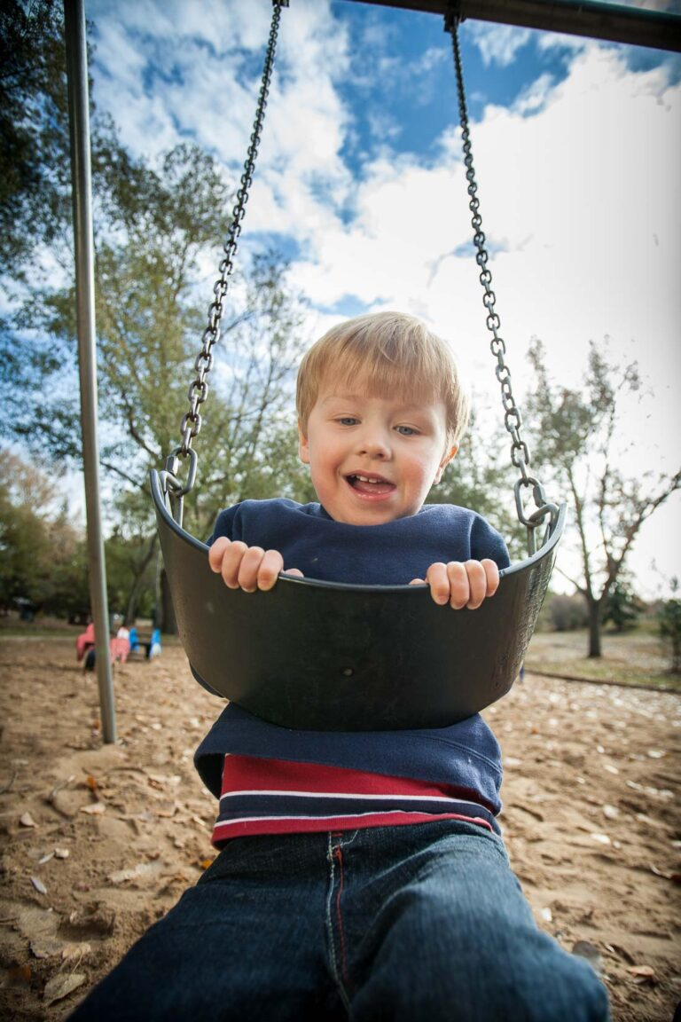 a fun portrait example of a child on a swing taken with a wide angle lens